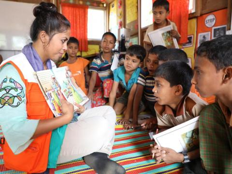 World Vision child protection coordinator Shampa Kundu reads a story book to children attending World Vision's Multi-Purpose Child and Adolescent Centre in the Rohingya refugee camp in Cox's Bazar, Bangladesh.