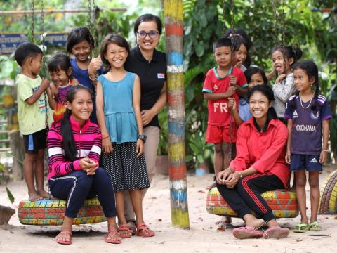 Khmer girl stands with World Vision Cambodia staff member and other children from her community
