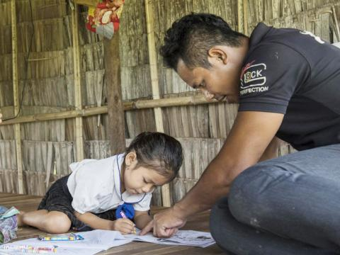 Khmer father helping his daughter with her school work inside their home, Cambodia. Parents involved in child's education