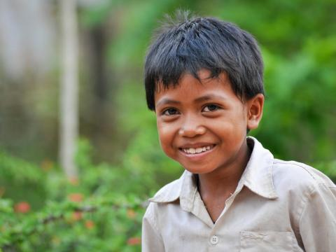 Khmer boy smiles at the camera with lush green foliage behind him.