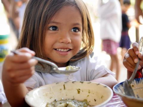 Khmer girl ginning as she holds spoon with nutritious porridge, Cambodia.