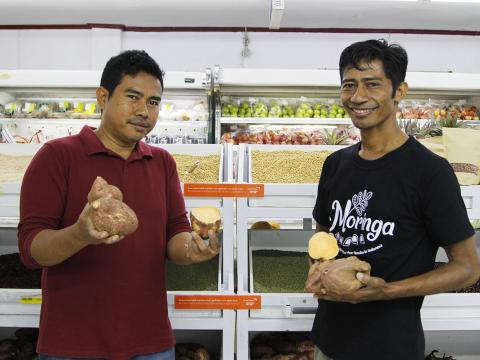 Leader supermarket manager, Teofilho da Silva (left) and World Vision's economic development specialist, Jesuinho Gusmão show local produce from Bobonaro farmers. Photo: Seung Eun Lim/World Vision