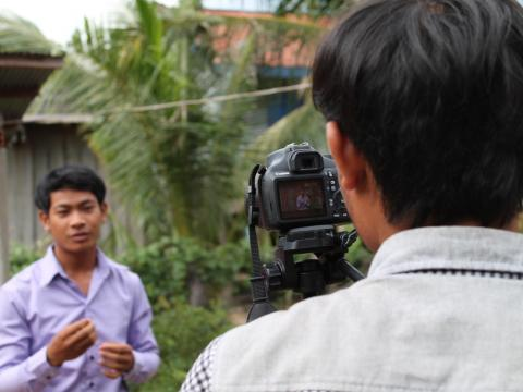 Khmer youth films his friend with DSLR camera on a tripod, youth participation