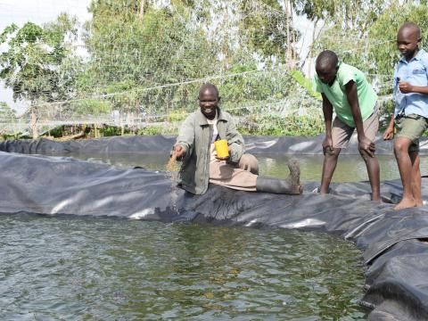 James feeding fish at one of his ponds with his sons. World Vision/Photo by Sarah Ooko.