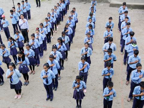 Students of Kalika Devi School sing the national anthem during morning assembly