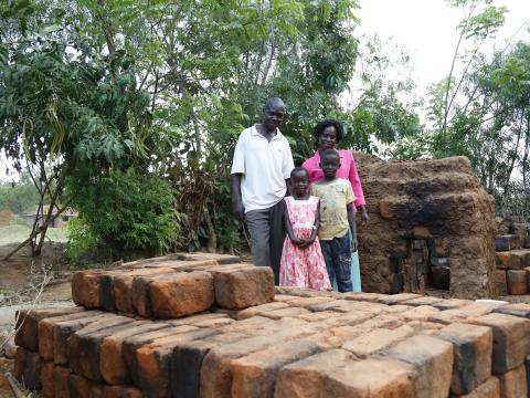 Joseph with his wife Joan and two of their children, Dalmas and Skovia, at their brick making site in their home in Busia, Kenya. ©World Vision/Photo by Susan Otieno.