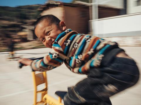 A child in Asia rides a scooter