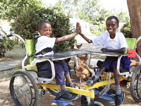 Gift (right)and his friend play at Masaku Primary School in Kenya's Machakos County. The wheelchairs, donated by World Vision, have enabled the children perform tasks independently and play with friends. @World Vision Photo/By Hellen Owuor.