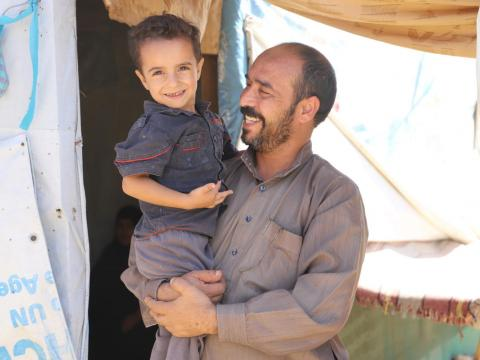 Syrian refugee Ayman in front his tent with his child