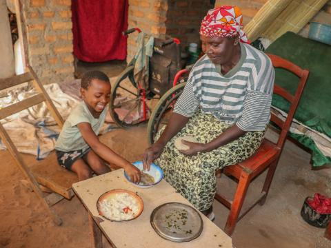 Josephine and her grandchild Maggie eating Nshima-- the staple food in Zambia made from finely ground corn meal, called mealie meal.