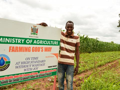 happy farmer standing next to a poster