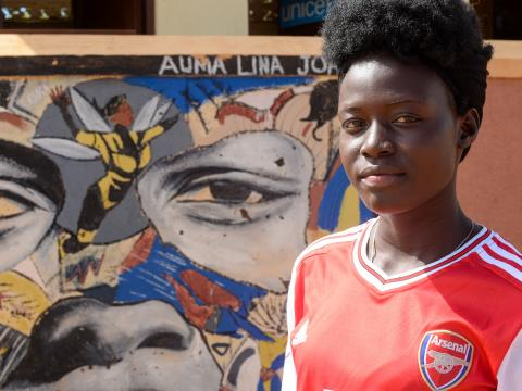 Lina Auma posing next to her superwoman portrait