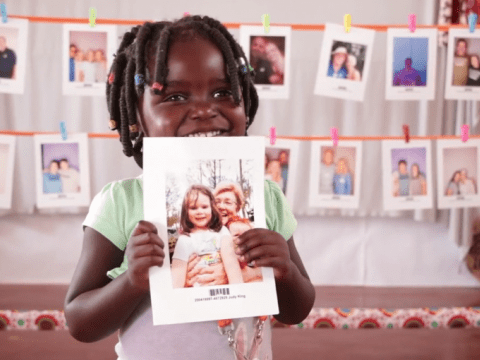 A child holds the picture of the sponsor they chose.