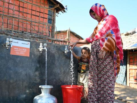 Shahanara, a Rohingya mother of three children, collects water from one of 30 water points in Camp 15 that provide chlorinated potable water to more than1,000 refugee and host community families. World Vision installed the innovative solar-powered water network, funded by Global Affairs Canada. Photo: Himaloy Joseph Mree, World Vision