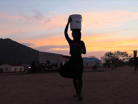 Woman holding water bucket over head