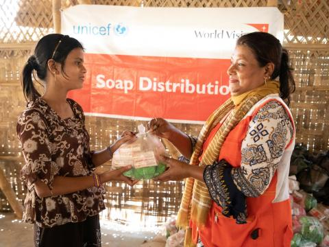 A child receives soap from a World Vision staffer
