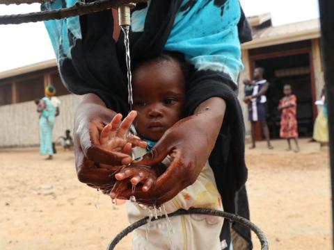 Mother washing he child's hand with clean water
