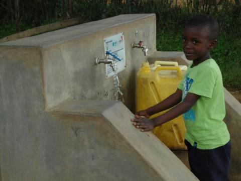 Chris fetching water from a safe & convenient water source.