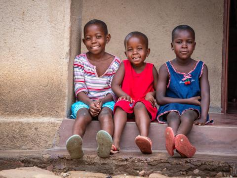 Three Zimbabwean children sitting on a step