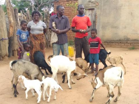 A farmer standing with his family members and goats