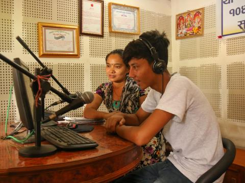 A community radio staff record an episode of a radio programme.