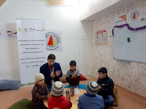 Adil (in the brown jacket to the left of facilitator Muath) participating in group activities in the Child Friendly Space