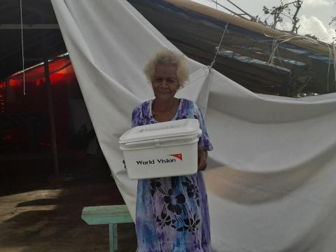 Elcy in front of her church with the hygiene kit