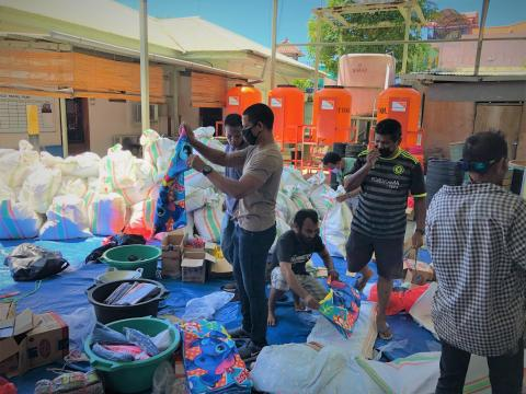 World Vision's Abilio Marques (standing in the middle while holding cloth) and the team packing the items.