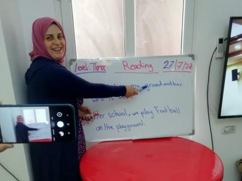 Nahed, remedial class teacher, explains a lesson on camera so as to send the video later to her students