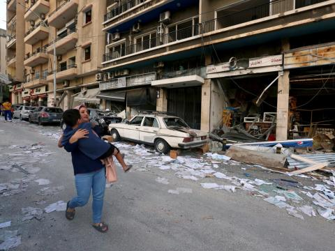 mother carries child through rubble along the streets of Beirut following deadly blast