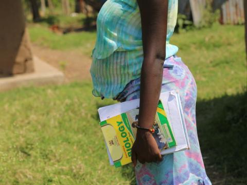 Young prengant girl from Africa holds school books in her hands