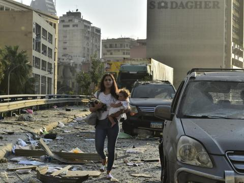Woman walks with child through the streets of Beirut following blast