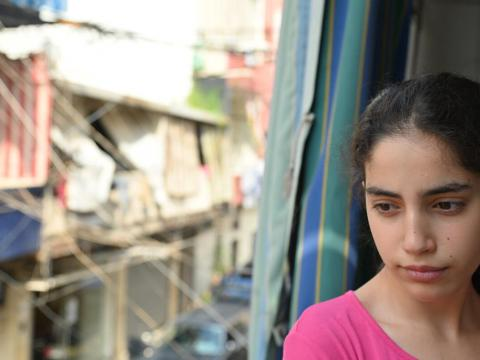 Girl child in Lebanon looking out window following catastrophic explosion