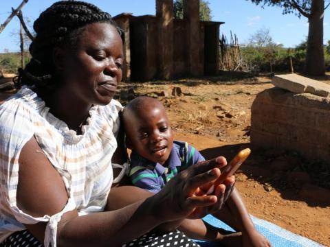 Mother and child use a phone for information and education in Zimbabwe