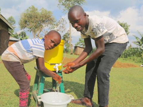 Raphael washing his hands with a younger child in Kenya