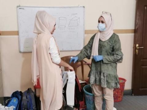 Hiba receiving school materials from World Vision case worker, Maryam.