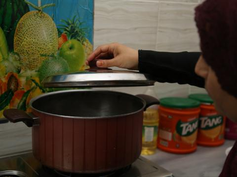 Full shot of Mrs. Bashaer placing the lid onto the cooker.