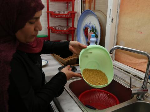 Medium shot of Mrs. Bashaer rinsing the bulgur.