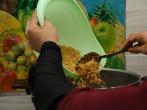 Close-up shot of Mrs. Bashaer adding the bulgur to the boiling water with lentils.