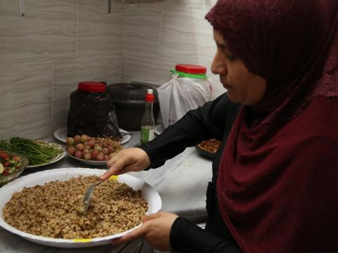 Over the shoulder shot of Mrs. Bashaer serving the Mujaddara onto a new plate.