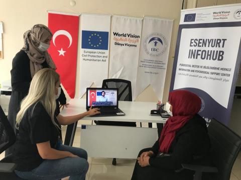 Refugees watching informative videos at IBC's info hub