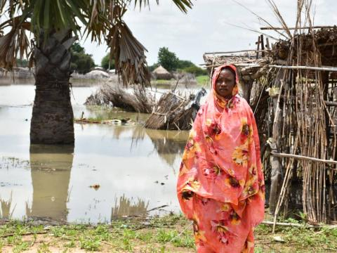 Sudanese woman stands in front of flooding