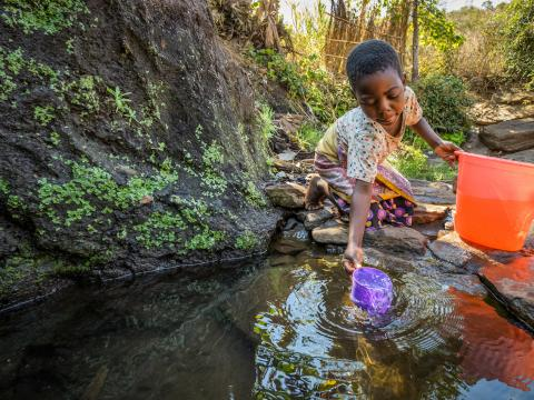 Irene collecting water from a stream in Malawi