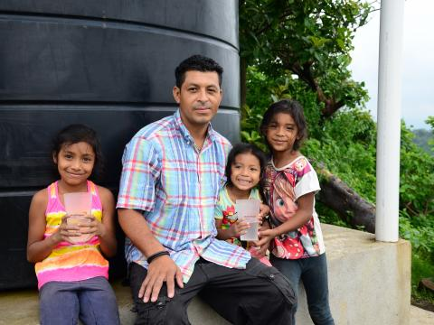 A family sit infront of a water tank