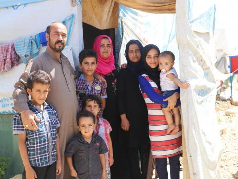A Syrian family outside their refugee shelter