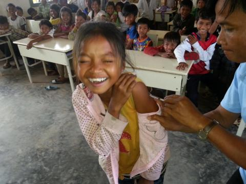 A smiling student gets a measles shot