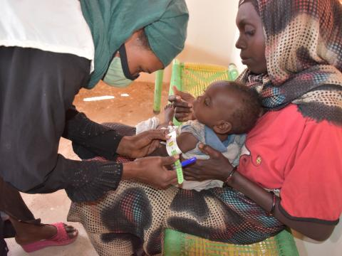 A World Vision nutrition nurse, attends to a child admitted with malnutrition, at a World Vision nutrition centre