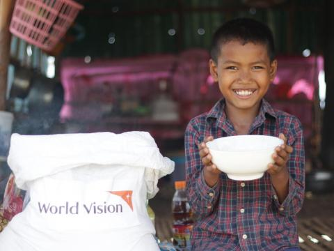 Young boy in Cambodia with bowl full or rice