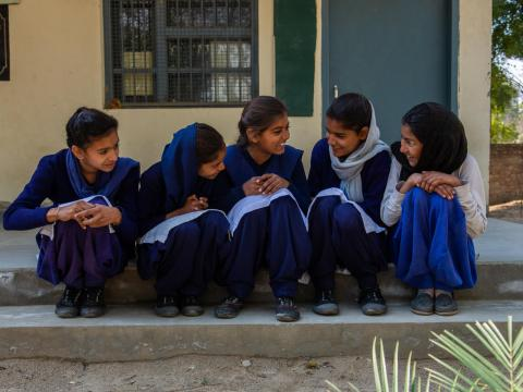 Girls in India sit on the step of the school, grateful for the opportunity to continue their education thanks to safe toilets