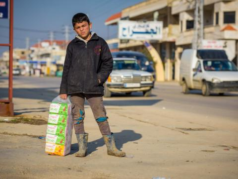 Ali, a Syrian refugee boy in the Bekaa Valley of Lebanon, sells tissues on the street to earn money for his family.